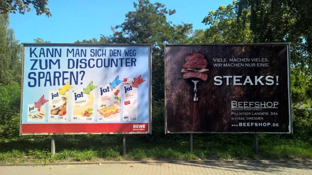 Abituraufgabe Flüchtlingskrise – Bild zweier Werbetafel zu Billigprodukten und einem Fleischshop